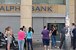 People stand in a queue to use ATMs of a bank in Athens. Greece's fraught bailout talks with its creditors took a dramatic turn early Saturday, with the radical left government announcing a referendum in just over a week on the latest proposed deal - and urging voters to reject it.