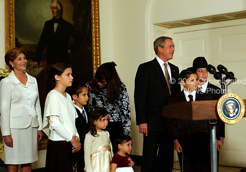 Felzenberg family and  United States President George W. Bush and first lady Laura Bush listen to a performance by Kol Zimra, an a cappella choir which sang two Chanukah songs, at the White House in Washington, D.C. on December 9, 2004.  For the past three years, the President has participated in a Menorah lighting before the annual White House Hanukkah Reception.&nbsp;Her father, Captain Shmuel Felzenberg, is serving in Iraq as the senior Jewish chaplain with the United States Army's 84th Engineer Battalion, from Schofield Barracks, Hawaii. Captain Felzenberg is scheduled to return home in January.  The four-foot-tall sterling silver Menorah is on loan from the Boca Raton Synagogue in Boca Raton, Florida. The Menorah was made in Israel and purchased for the synagogue by two congregants, Nachman and Jamie Feig.&nbsp;Because tonight is the third night of Chanukah, the lighters will light three candles and the shamash, the main candle. From left to right: First lady Laura Bush; Miriam Felzenberg; , Dovid, Freida, and Ahuva Felzenverg; Nechama &quot;Dini&quot; Felzenberg (speaking to Dovid); President Bush; Chaim Felzenberg; Menachem Felzenberg.<br /> Credit: Ron Sachs / Pool via CNP