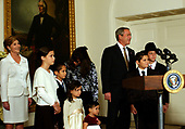 "Felzenberg family and  United States President George W. Bush and first lady Laura Bush listen to a performance by Kol Zimra, an a cappella choir which sang two Chanukah songs, at the White House in Washington, D.C. on December 9, 2004.  For the past three years, the President has participated in a Menorah lighting before the annual White House Hanukkah Reception. Her father, Captain Shmuel Felzenberg, is serving in Iraq as the senior Jewish chaplain with the United States Army's 84th Engineer Battalion, from Schofield Barracks, Hawaii. Captain Felzenberg is scheduled to return home in January.  The four-foot-tall sterling silver Menorah is on loan from the Boca Raton Synagogue in Boca Raton, Florida. The Menorah was made in Israel and purchased for the synagogue by two congregants, Nachman and Jamie Feig. Because tonight is the third night of Chanukah, the lighters will light three candles and the shamash, the main candle. From left to right: First lady Laura Bush; Miriam Felzenberg; , Dovid, Freida, and Ahuva Felzenverg; Nechama ""Dini"" Felzenberg (speaking to Dovid); President Bush; Chaim Felzenberg; Menachem Felzenberg.<br /> Credit: Ron Sachs / Pool via CNP"