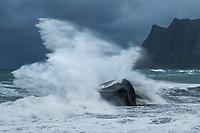 Large wave crashes into rock at Uttakleiv beach, Vestvågøy, Lofoten Islands, Norway