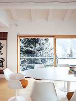 The white Eero Saarinen Tulip table and chairs in the dining area appear sculptural against the dark shape of the snow-covered fir tree beyond the sliding window
