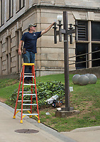 NWA Democrat-Gazette/SPENCER TIREY    Mike Ball with the University of Arkansas Electrical Shop retrofits a light pole that had Metal Halogen lights Friday Sept. 8, 2018, to LED lights outside the Bell Engineering building on the Fayetteville campus. The University is slowing changing out older Halogen lights on the campus walkways to LED.