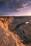 Sunset light on sheer sandstone cliffs above the Colorado River Canyon at Horseshoe Bend, near Page, Arizona