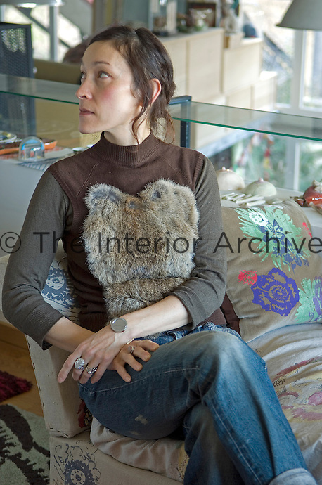 Portrait of artist Nathalie Lete sitting on the end of her sofa looking away from camera
