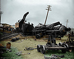 While this scene includes human spectators in the left background, the photographer has positioned the camera so that the two handcars in the right foreground also appear to be observing the fallen steam engine. The derailed and toppled locomotive bears the name plaque 2040 on the front of the engine. One of the derailed cars in the background is painted with the initials CRI&P of the Chicago, Rock Island and Pacific Railroad. A rail-mounted crane is in the process of lifting the tender away from its wrecked locomotive. Rock Island Railroad built its line through Lincoln in 1892, the last of several railroads to add service to Lincoln. Abandoned in the 1970s, the Rock Island right-of-way is now one of several bicycle trails through the city.