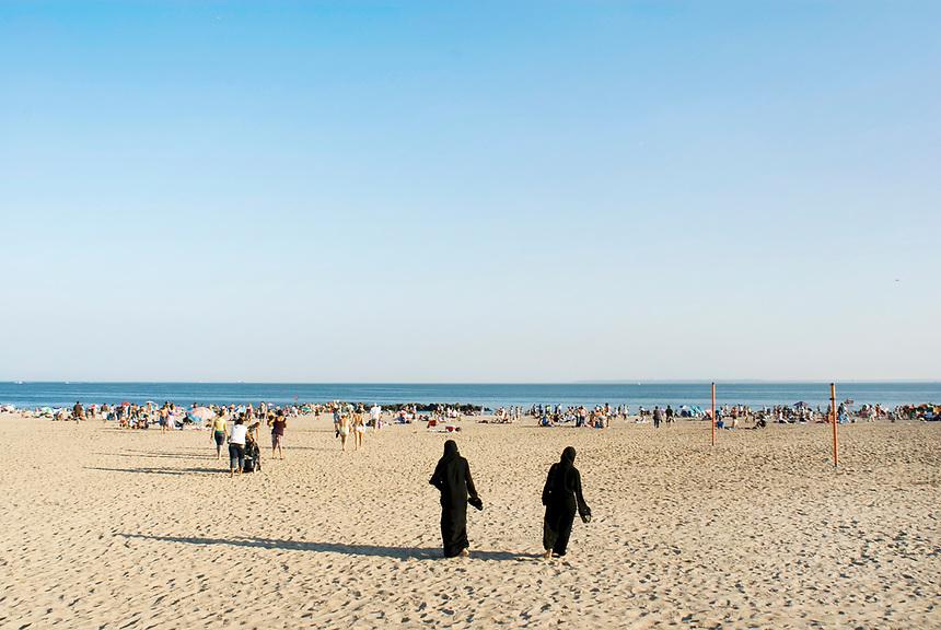 Two muslim women walk across the crowded beach in Coney Island. Street photography in Coney Island, Brooklyn,  NY August 4, 2007