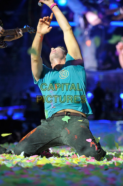 Chris Martin of Coldplay .performing live in concert at the Emirates Stadium, London, England, UK,.1st June 2012..music gig on stage half length turquoise t-shirt jeans full paper confetti butterflies kneeling half arms raised up .CAP/MAR.© Martin Harris/Capital Pictures.