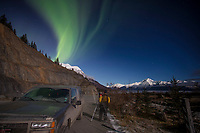 winter landscape shows photographer taking photos of Northern Lights (Aurora Borealis) in sky above moonlight on the Chugach Mountains along Turnagain Arm and Seward Highway  January 2014