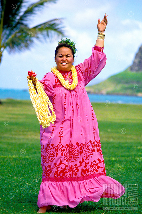A Hawaiian woman wearing a pink muumuu and several strands of pikake lei draped on her arm stands in a hula pose on the grass at Kualoa Park