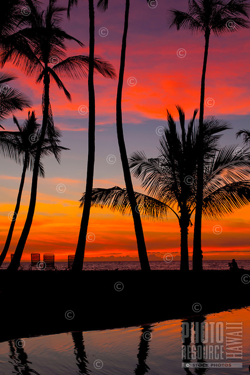 A beachgoer sitting in a chair on Waikoloa Beach takes in the sunset off 'Anaeho'omalu Bay, Big Island.