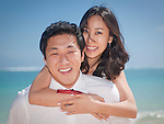 Asian bride rides on groom's back while they stroll on Lanikai beach as they look forward to their life as a married couple following their wedding.