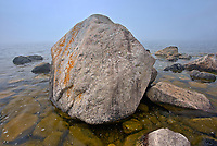 Large rocks and bolders on shoreline of Lake Superior in fog at Katherine Cove <br />