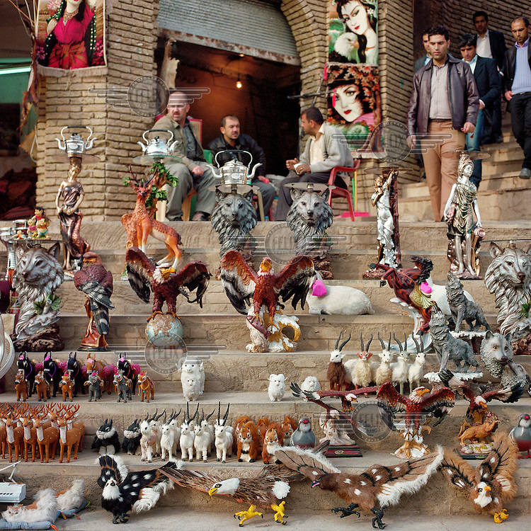 Street vendors sell souvenirs including statues of eagles, wolves and rams at a stall at the entrance to the ancient Citadel of Arbil. The Citadel of Arbil is an inhabited mound in the centre of the modern Iraqi city of Erbil, which is said to be one of the oldest, continually inhabited places in the world. Earliest traces of habitation on the mound date back to the 5th millennium BC, possibly earlier. The city of Erbil, the fourth biggest in Iraq, is today the capital of Iraqi Kurdistan. .Since 2007 the High Commission for Erbil Citadel Revitalisation (HCECR) has been in charge of the Citadel complex and is carrying out major reconstruction efforts since moving out all remaining residents. It is hoped that 50 families will move back into the Citadel once renovation work and archeological digs have been completed. .