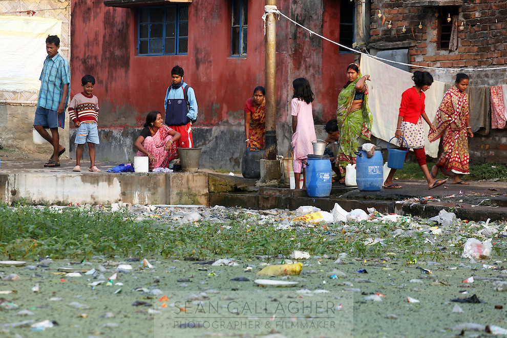 Residents of the Captain Bherry community in Kolkata gather around a water pump in the early morning. In the foreground a small pond is suffering from eutrophication, a phenomenon caused by excessive nutrients being released into the water, resulting in the proliferation of algae on the surface and subsequent death of aquatic life below. India. November, 2013