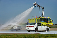 NWA Democrat-Gazette/BEN GOFF &bull; @NWABENGOFF<br /> A Northwest Arkansas Regional Airport fire truck sprays fire-retardant foam on vehicles on Saturday Aug. 8, 2015 during a full-scale training exercise at the airport in Highfill. The exercise for agencies in Benton County that respond to emergencies at the airport simulated a plane crash scenario.