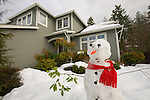 Snowman in front of House