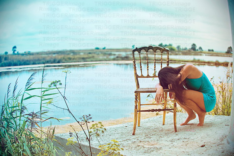 Full body portrait of a young woman resting her head on a golden chair, with a lake in the background and the horizon looking like she is in a bubble.