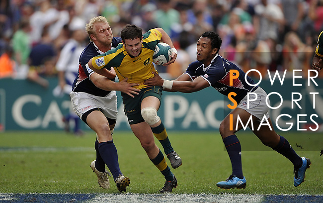 HONG KONG - MARCH 28:  Robbie Coleman (C) of Australia eledes a tackle by USA players on day three of the IRB Hong Kong Sevens on March 28, 2010 in Hong Kong.  Photo by Victor Fraile / The Power of Sport Images