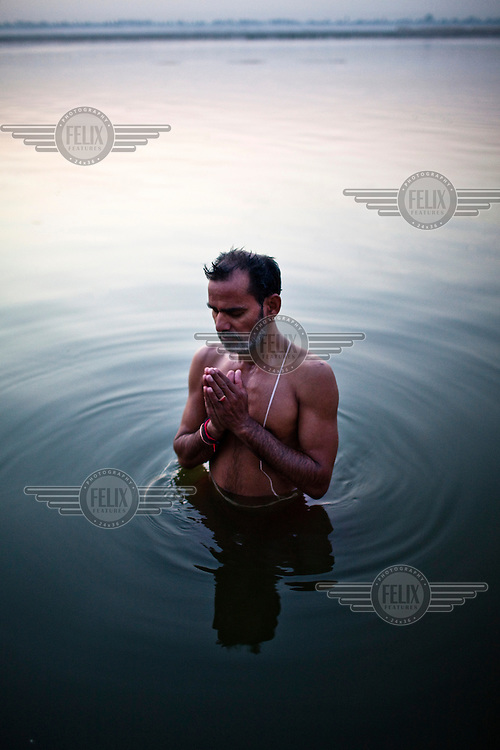 A religious Hindu priest offers prayers and takes a bath at dawn on the ghats of the Ganges River in the ancient city of Varanasi.