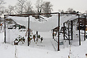 A heavy fall of snow weighs down the netting on the roof of a fruit cage, stretching it and risking it tearing. Nets should be removed from roofs over winter.