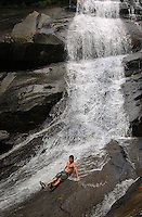 A visitor cools off in the Harper Creek Waterfall in the North Carolina mountains. No model release. Editorial only.