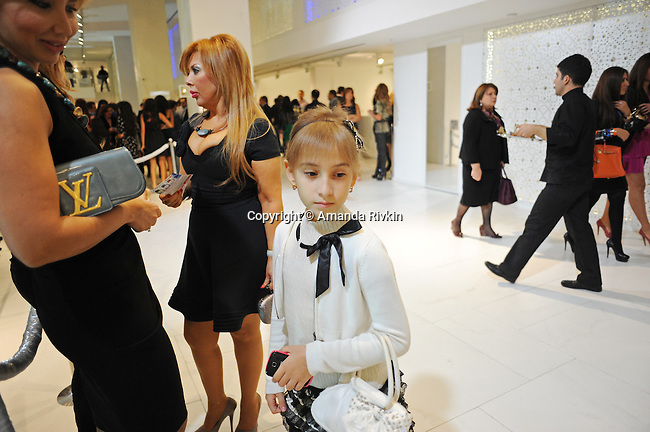A young girl wearing Jean Paul Gautier stands with her smartphone and purse in hand beside her mother and a companion at the grand opening celebration of Emporium's second store at the still under construction Port Baku seaside luxury residences in the Azeri capital of Baku, Azerbaijan on October 28, 2011.  Emporium's second store in Baku was designed by Japanese architect Yukio Ishiyama of the Milanese design firm Garde and features over 150 luxury ready-to-wear brands such as Azzedine Alaïa, Marc Jacobs and Stella McCartney; Emporium is widely considered to offer the greatest variety of high-end designer shopping in Baku under one roof.