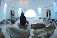 Sweden, SWE, Kiruna, 2006-Apr-12: Visitors viewing the chapel belonging to the Jukkasjarvi icehotel. For protection against the cold the seats are covered with reindeer skins.
