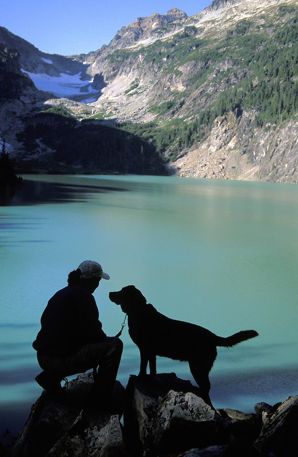 Woman and dog silhouetted against green lake, Blanca Lake, Mount Baker-Snoqualmie National Forest, Cascade Mountains, Washington
