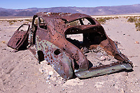A rusted, bullet riddled, and sand blasted automobile sits on the floor of the Panamint Valley in Death Valley National Park