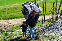 Pictured: Migrants of all ages, carrying their belongings, make their way through fields to Idomeni, Greece Wednesday 02 March 2016<br />