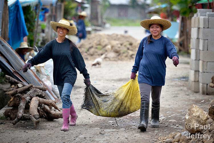 Merlita Abad (left) and Janilyn Canama help to clean up their community following Typhoon Haiyan, removing refuse from blocked drainage ditches as part of a cash for work program sponsored by Lutheran World Relief, a member of the ACT Alliance. Their neighborhood in Ormoc, a city in the Philippines province of Leyte, was hit hard by the typhoon, known locally as Yolanda, in November 2013. LWR and other ACT Alliance members have been providing a variety of forms of assistance to survivors here.