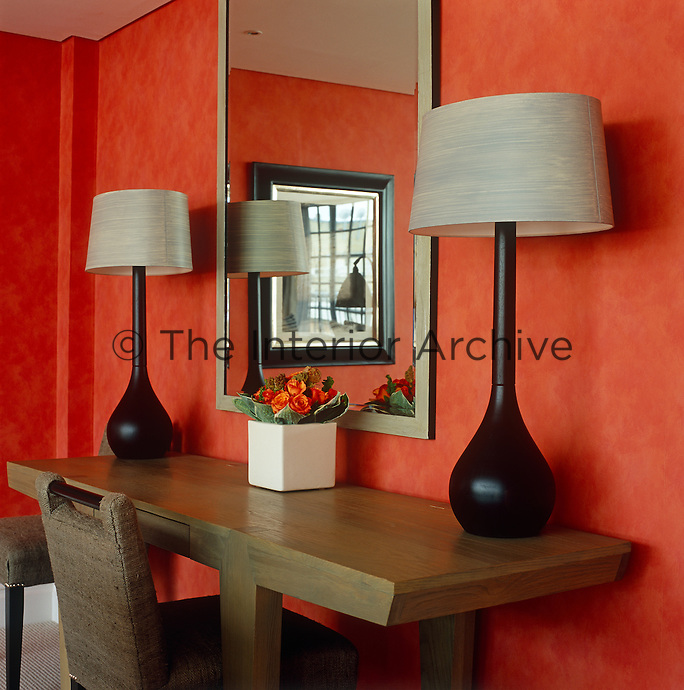 Two matching black table lamps on either side of the central mirror create a symmetry in this London hotel room
