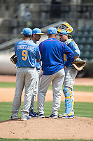 Myrtle Beach Pelicans pitching coach David Rosario has a chat on the mound with catcher Victor Caratini (17), pitcher Jonathan Martinez (40), and third baseman Jeimer Candelario (9) during the game against the Winston-Salem Dash at BB&T Ballpark on May 10, 2015 in Winston-Salem, North Carolina.  The Pelicans defeated the Dash 4-3.  (Brian Westerholt/Four Seam Images)