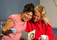 Women having coffee and laughing while reading a greeting card.