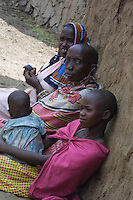 Three generations of Maasai wives gather on the outside of one of their dung and ash homes to pass the time.  Each home is part of the circular shaped village called a Manyata.  Building each marital home is the responsibility of the girl once she is married.  In the Maasai Mara, like many other places throughout the world, forced early marriages of children is considered to be a part of the culture.  Since the number of wives is indicative of a man's wealth, a girl as young as nine years old can be sold into marriage with a man who already has up to ten wives. Before marriage, the girls must undergo FGM (Female Genital Mutilation) also known as FGC (Female Genital Cutting).  In Kenya, it is now an illegal practice to marry a child bride, however most homesteads are situated in rural locations where it remains difficult to monitor such activity.