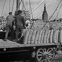 Hafenarbeiter im Hafen von Elbing, im Hintergrund die Nikolaikirche, Masuren, Ostpreußen, Deutschland 1930er Jahre. Workers at Elbing harbor, in the background St. Nicolas church, Masuria, East Prussia, Germany 1930s.