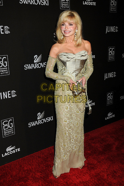 LONI ANDERSON .Attending the 12th Annual Costume Designers Guild Awards held at the Beverly Hilton Hotel.  .Beverly Hills, California, USA,  .25th February 2010 .arrivals full length long maxi dress sleeves arm warmers green plastic surgery cosmetic strapless smiling gold earrings beige lace gold fan shaped bag .CAP/ADM/BP.©Byron Purvis/AdMedia/Capital Pictures.