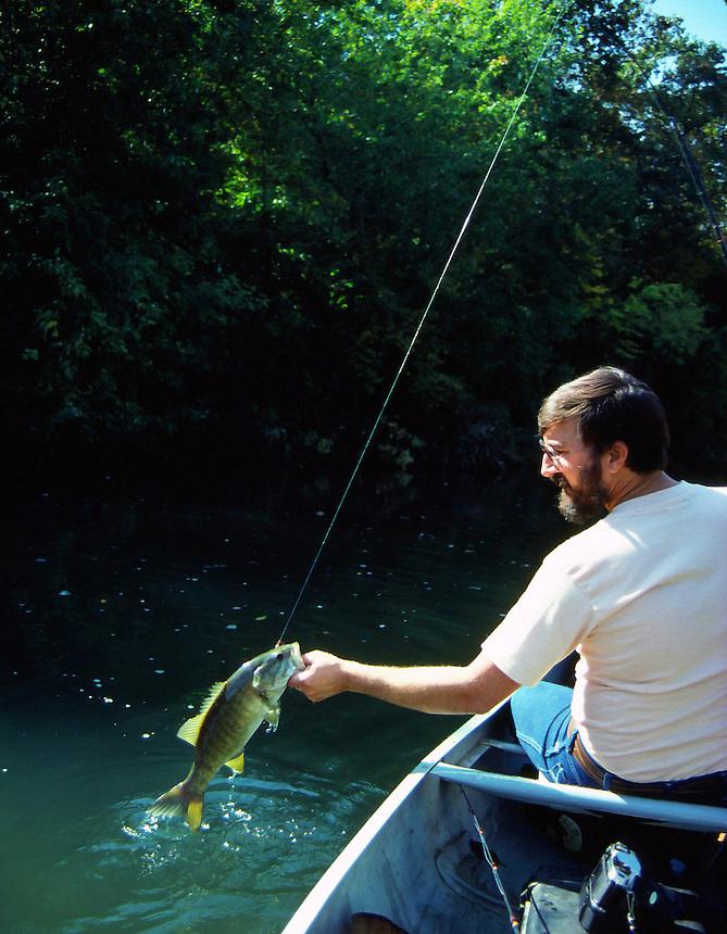 Angler landing smallmouth bass on Upper Ouachita River, Arkansas