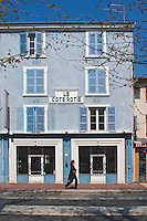 A bright blue house on an empty street, two shop windows shopwindows closed with iron shutters and a sign Le Cote Rotie in the village. A woman walking in front of the house. Ampuis, Cote Rotie, Rhone, France, Europe