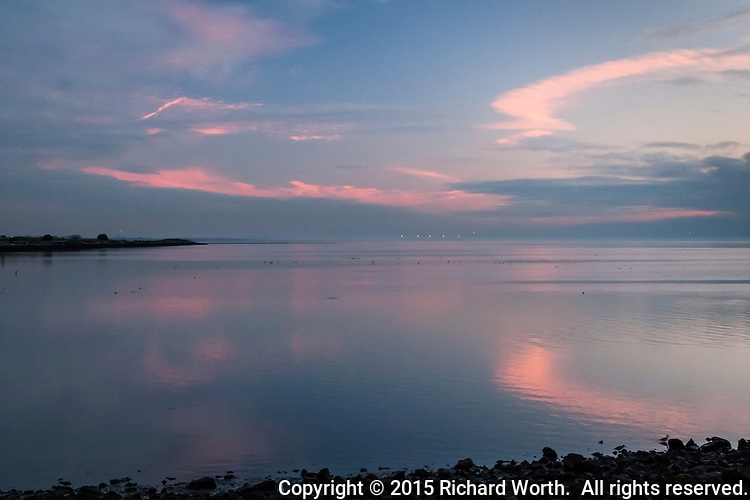 Traces of pink clouds are reflected in the waters of San Francisco Bay after sunset on a winter evening.