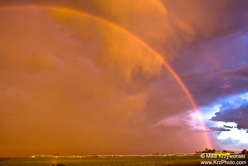 Rainbow across an orange stormy sky at sunset in Fort Morgan, CO