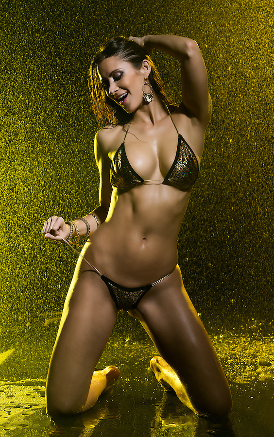 Sensual model in bikini with water behind very playful under yellow light