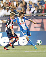 Philadelphia Union midfielder Michael Farfan (21) crosses the ball as New England Revolution midfielder Scott Caldwell (6) closes. In a Major League Soccer (MLS) match, the New England Revolution (dark blue) defeated Philadelphia Union (light blue), 5-1, at Gillette Stadium on August 25, 2013.Philadelphia