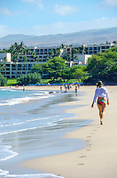 Woman walking at Hapuna Beach, along the Big Island's Kohala Coast. This white sand beach has been rated one of the best beaches in the world. Hawaii Prince Resort is at the north end of the beach.