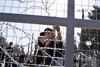 MAZEDONIEN, 01.03.2016, Gevgelija. Internationale Fluechtlingskrise auf der Balkanroute: Fluechtlinge und Migranten, warten auf der griechischen Seite der mit einem Zaun gesperrten Grenze darauf, ihre Reise nach Norden fortsetzen zu koennen. Teilweise haben sie Blumen gepflueckt. Am Vortag war es zum Traenengaseinsatz gekommen, als Leute den Zaun stuermten und zu ueberwinden versuchten. | International refugee crisis on the Balkan route: Refugees and migrants at the fence waiting on the Greek side of the closed border to proceed their journey to the North. Some come with flowers they picked. The day before Macedonian police fired tear gas at people storming the border fence trying to get through.<br /> © Tomislav Georgiev/EST&OST