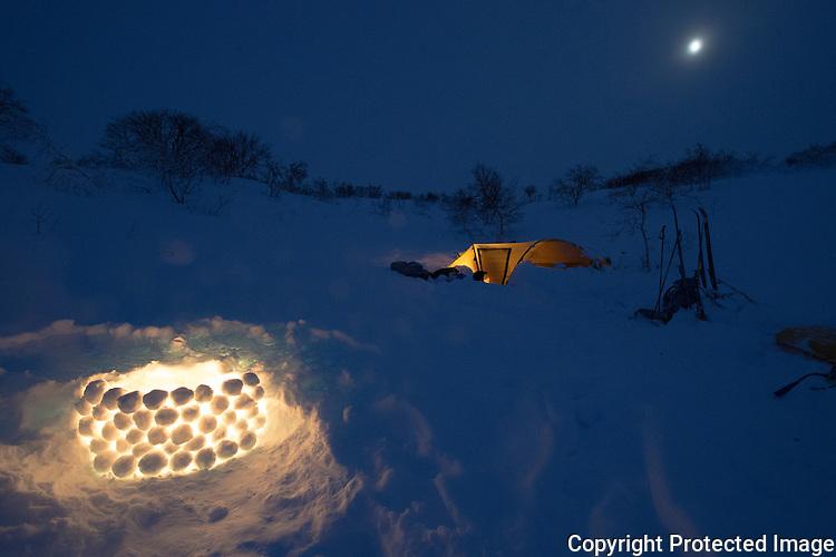 Snølykt ved teltleir i blåtimen. ---- Candlelight in tent camp.