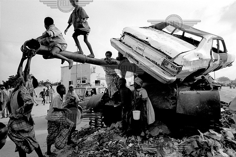 © Paul Lowe / Panos Pictures..MOGADISHU, SOMALIA AUGUST 1992.DURING THE FAMINE, CAUSED BY CIVIL WAR AND RACKETEERING, CHILDREN PLAY ON A THE WRECKAGE OF AN AMERICAN CAR AND A RUSSIAN TANK. COPYRIGHT PAUL LOWE. NO PHOTOGRAPH OR DIGITAL FILE MAY BE REPRODUCED, CROPPED OR DIGITALLY MODIFIED IN ANY MEDIUM AND ITS CAPTION MAY NOT BE ALTERED WITHOUT THE PRIOR WRITTEN AUTHORISATION OF THE PHOTOGRAPHER OR HIS AGENT.