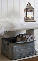 An old zinc box is used to store magazines under this painted bench in the dining area