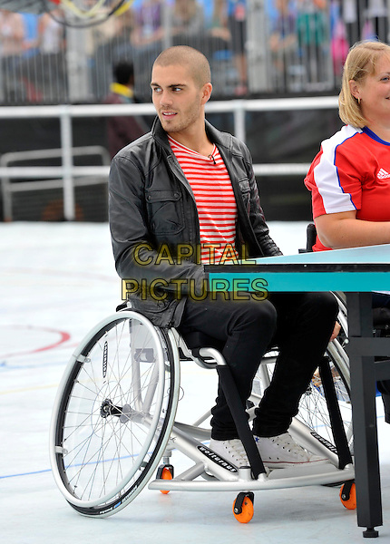 The Wanted - Max George .London - Members of boyband 'The Wanted' play 'wheelchair table tennis' as part of the Sainsburys Super Saturday. The event raises funds for the Paralympic Legacy Fund and celebrates one year to go until the Paralympic Games.  London, England..September 10th 2011.band group sitting black leather jacket sitting jeans denim red stripe top table sport paddle  ping pong full length.CAP/ROS.©Steve Ross/Capital Pictures