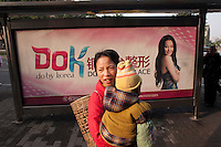 A Woman Holding A Child At A Bus Stop In Front Of Do By Korea Signage In Chongqing, China.  © LAN